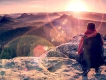 chiarore Equipaggia il sitt sul bordo della scogliera e lo sguardo al sol levante sopra la valle fotografia stock libera da diritti