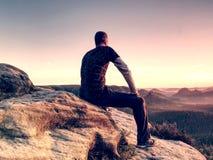 chiarore Equipaggia il sitt sul bordo della scogliera e lo sguardo al sol levante sopra la valle immagini stock
