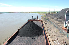 Chiatta con carbone al porto fluviale Kolyma Immagine Stock