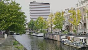 Chiatte e case galleggianti al canale di Amstel a Amsterdam, Paesi Bassi archivi video