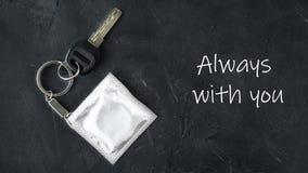 Chiave con keychain con stagnola grigia falsa sul preservativo come catena dell'orologio sul fondo vuoto nero della lavagna con t fotografia stock libera da diritti