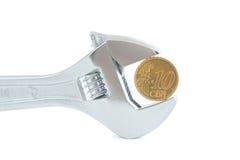 Chiave d'acciaio con la moneta isolata su bianco Fotografie Stock