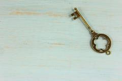 Chiave d'ottone antica su un fondo di legno afflitto verde pallido Fotografie Stock