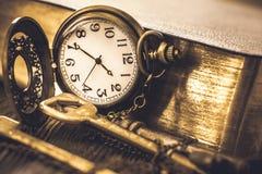 Chiave decorativa dell'oggetto d'antiquariato e dell'orologio da tasca da un libro Fotografie Stock