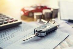 chiave dell'automobile con soldi ed il calcolatore sulla tavola finanza di concetto e fotografia stock