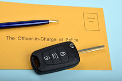 Chiave dell'automobile con una busta blu della polizia e della penna Fotografie Stock