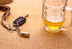 Chiave dell'automobile con una tazza inclinata di birra e del rimorchio Fotografia Stock Libera da Diritti