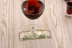Chiave dell'automobile e del bicchiere di vino su un fondo di 100 banconote in dollari concetto da smettere bere fotografie stock libere da diritti