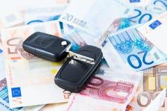 Chiave dell'automobile sul fondo dei soldi Immagini Stock