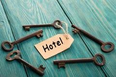 chiave dell'hotel con l'etichetta sui precedenti di legno Fotografia Stock