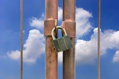 Chiave di catenaccio sul recinto arrugginito Fotografia Stock