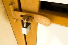 Chiave di catenaccio sulla vecchia porta del metallo giallo fotografie stock