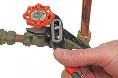 Chiave di s del ` dell'idraulico che stringe una valvola Fotografia Stock Libera da Diritti