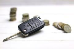 Chiave e moneta dell'automobile su fondo Immagine Stock