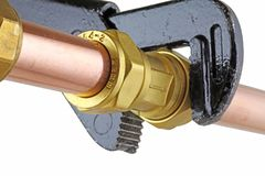 Chiave inglese del ` s dell'idraulico che stringe canalizzazione di rame fotografie stock libere da diritti