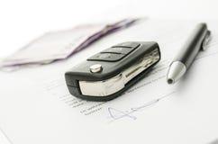 Chiave dell'automobile su un contratto della vendita dell'automobile Fotografia Stock