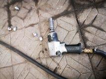 Chiave pneumatica con un tubo flessibile lungo che si trova sul pavimento delle mattonelle di pietra, vista superiore fotografia stock