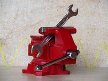 Chiave riparata in un vizio rosso su fondo leggero immagine stock libera da diritti