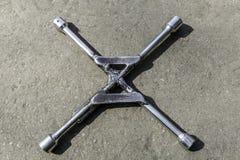 Chiave a ruote su asfalto con 4 estremità fotografie stock