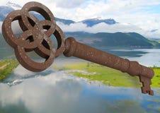 chiave rustica 3D che galleggia sopra il paesaggio verde Immagini Stock Libere da Diritti