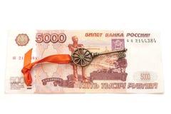 Chiave a successo con l'arco rosso sulla banconota della rublo russa 5000 Immagine Stock