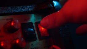 Chiavetta dell'interruttore di accensione che è girata in funzione e a riposo dal musicista Indicatore luminoso al neon variopint stock footage