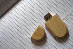 Chiavetta USB con superficie di legno alla pagina della nota per il computer portatile alimentabile del computer della porta USB  Fotografia Stock
