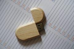 Chiavetta USB con superficie di legno alla pagina della nota per il computer portatile alimentabile del computer della porta USB  Fotografie Stock