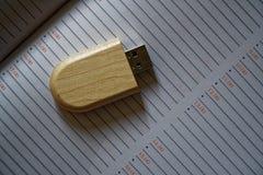 Chiavetta USB nella superficie di legno alla pagina della nota per il computer portatile alimentabile del computer della porta US Fotografia Stock Libera da Diritti