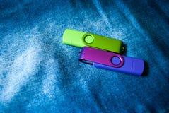 Chiavette USB porpora e verdi chiuse su un fondo dei jeans Fotografia Stock Libera da Diritti