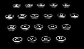 Chiavi antiche d'annata della macchina da scrivere su un fondo nero immagini stock
