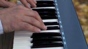 Chiavi bianche e nere del sintetizzatore I giochi di mani del pianista sul piano elettronico stock footage