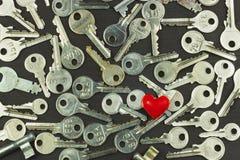 Chiavi d'argento su un bordo di legno scuro Tipi differenti di tasti Tasto al cuore Simbolo di amore Fotografie Stock Libere da Diritti