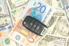 Chiavi dall'automobile su soldi Immagini Stock