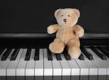 Chiavi del piano con la seduta teddybear Immagine Stock