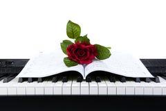 Chiavi del piano e fiore rosa sul taccuino Fotografia Stock
