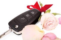 Chiavi dell'automobile con il nastro ed i fiori come regalo isolato su bianco Fotografia Stock Libera da Diritti