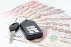 Chiavi dell'automobile e baht dei soldi su un fondo bianco Fotografia Stock Libera da Diritti