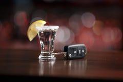 Chiavi dell'automobile e della bevanda alcolica sotto fotografia stock libera da diritti