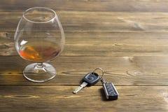 Chiavi dell'automobile e un vetro con alcool su un alcool di legno del fondo immagini stock