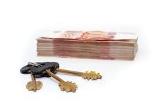 Chiavi della Camera che pongono dietro il mucchio di denaro contante Fotografie Stock Libere da Diritti
