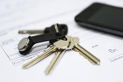 Chiavi della Camera sui documenti con il telefono cellulare Immagine Stock