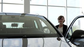 Chiavi della tenuta della giovane donna al nuovo veicolo, sorridente alla macchina fotografica, allegra video d archivio