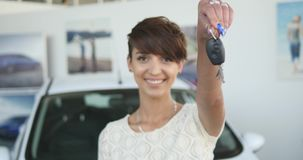 Chiavi della tenuta della giovane donna alla nuova automobile automatica e che sorride alla macchina fotografica stock footage