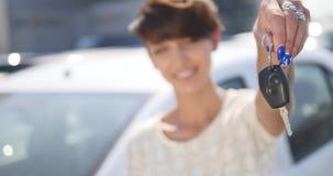 Chiavi della tenuta della giovane donna alla nuova automobile automatica e che sorride alla macchina fotografica archivi video