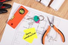 Chiavi domestiche con i diagrammi e gli accessori elettrici per l'organizzazione dei lavori, concetto domestico di costruzione Immagine Stock
