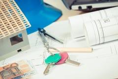 Chiavi domestiche, euro di valute, diagrammi elettrici ed accessori per i lavori dell'ingegnere, concetto domestico di costruzion Fotografie Stock