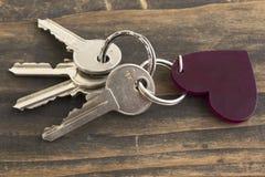 Chiavi e catena chiave del cuore su un fondo di legno rustico immagine stock libera da diritti