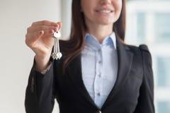Chiavi femminili della tenuta dell'agente immobiliare, acquisto della proprietà di acquisto Fotografie Stock