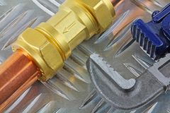 Chiavi inglesi che stringono T-montaggio sulla canalizzazione di rame di 15mm su un fondo bianco Fotografie Stock Libere da Diritti